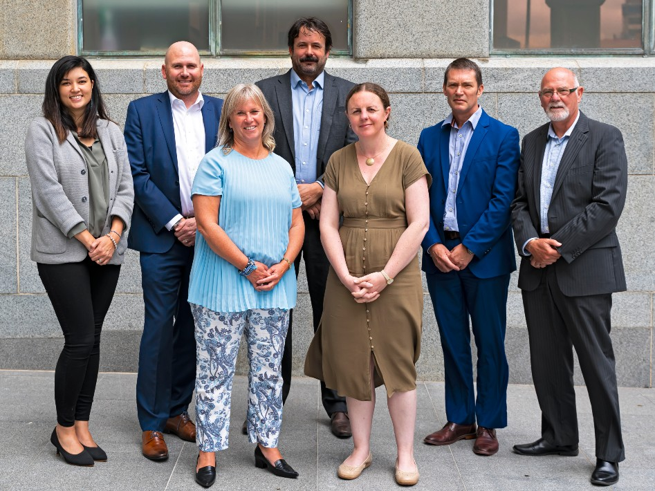 A team of people in office-wear stand together in front of a grey building wall.