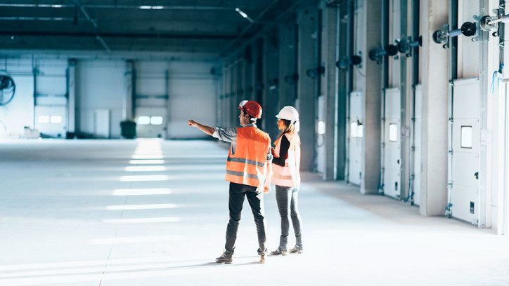A man and a woman in hard hats doing a facilities maintenance check