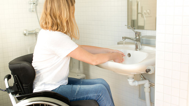 Woman in a wheelchair washing her hands
