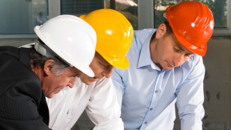 Three building professionals looking at design plans