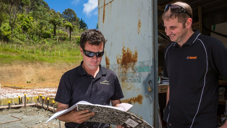 Two builders reviewing paperwork on site