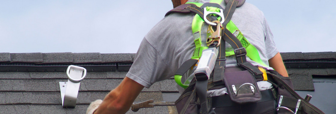 Roofer in safety harness