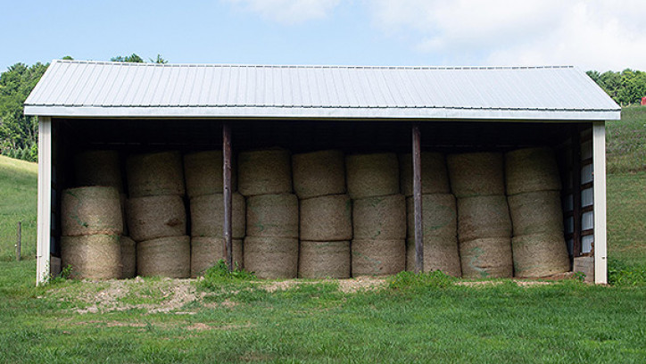 Lots of hay bales in open sided shed